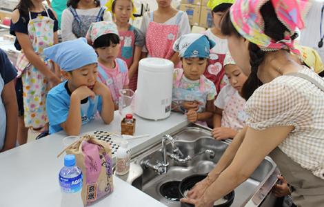 お米の研ぎ方を真剣に見ている子供