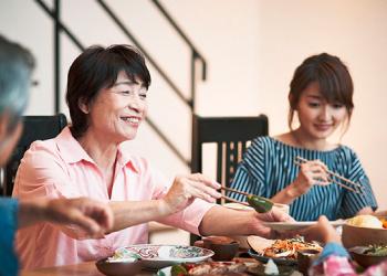 写真 家族でごはんを食べている